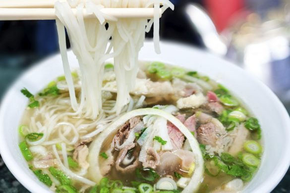 Bowl of Vietnamese pho noodle soup with rare beef, tendon, tripe and brisket served with onions, scallions and cilantro.
